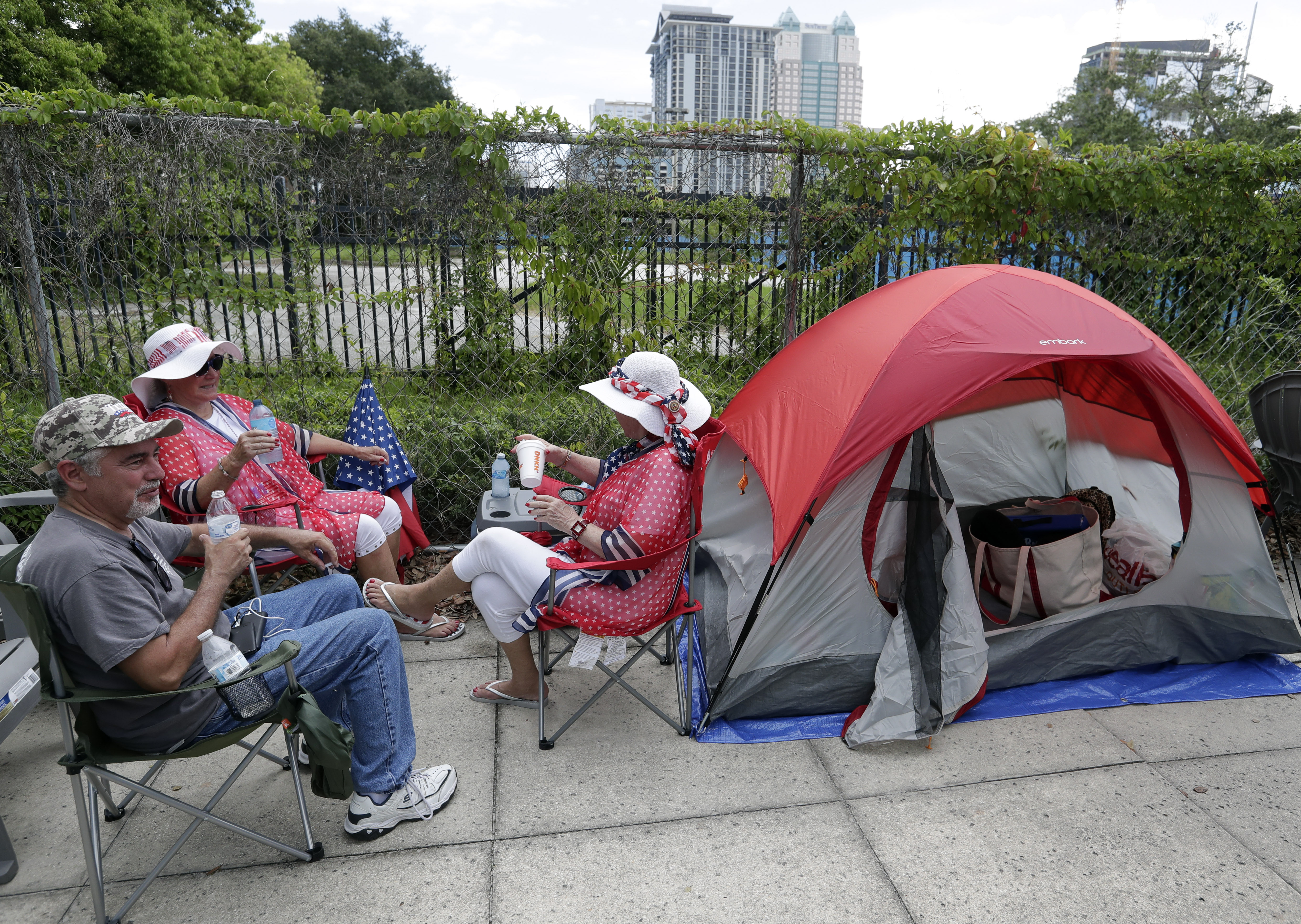 Supporters of President Donald Trump, from left, James DeWilde, Laureen Vartanian and Maureen Bailey wait in line with others on Monday, June 17, 2019, in Orlando, Fla. They are among the first people in line to attend a rally on Tuesday night. (AP…